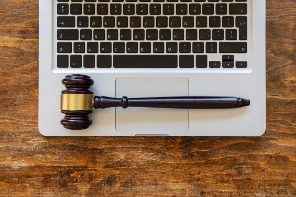 Judge gavel on a laptop, wooden background, top view. Online auction concept