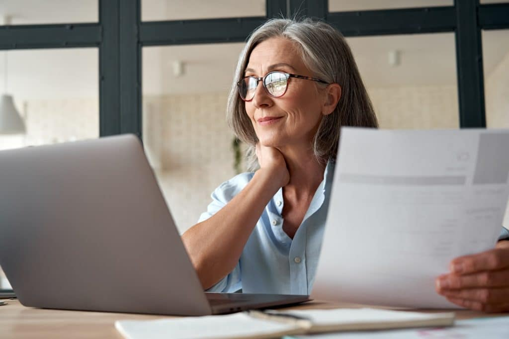 Smiling mature middle aged business woman holding cv searching job online.