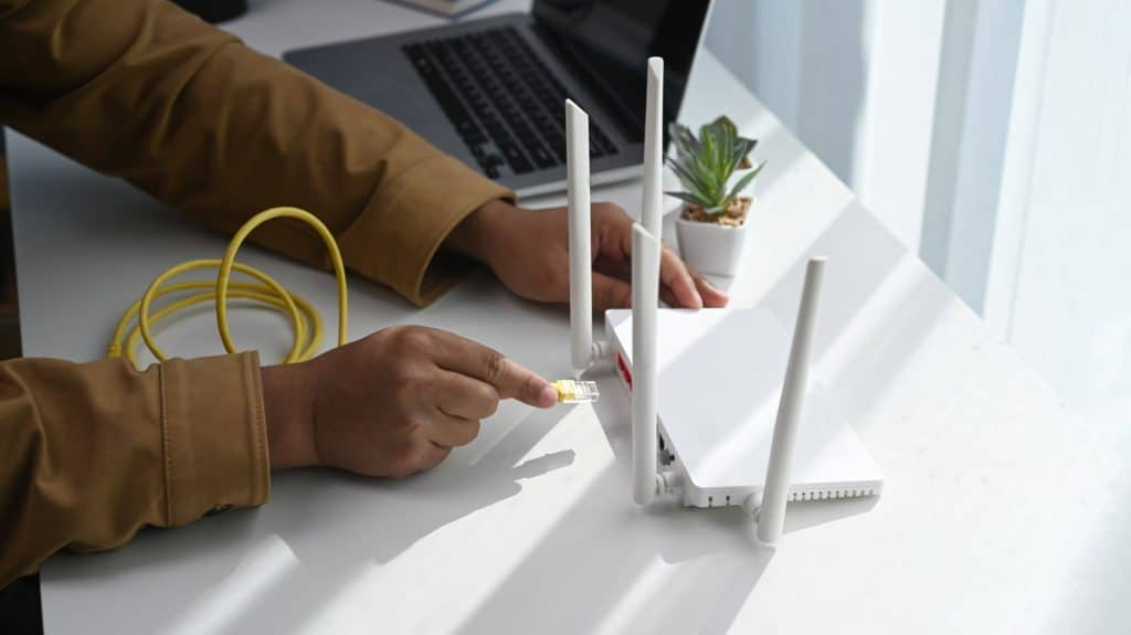 Close up view of man connects the internet cable to router socket. Wireless internet concept.